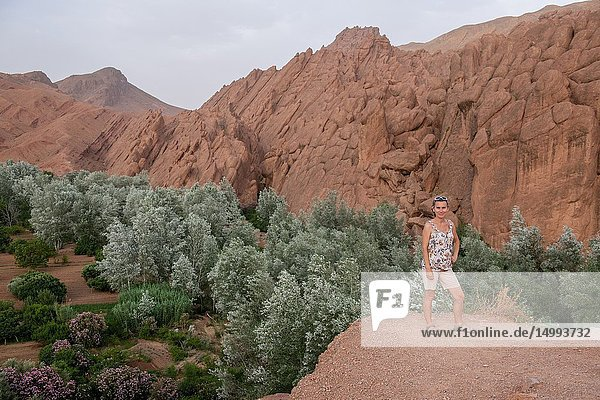 A female tourist poses for a photograph in front of the Atlas Mountain range,  Ouzazate,  Dades Gorge.