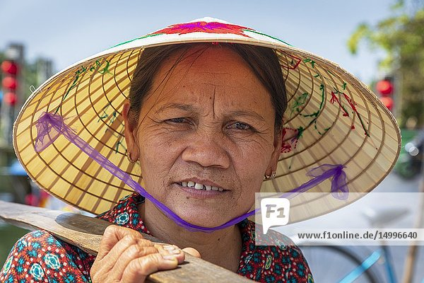 Portrait of an elderly Vietnamese woman wearing a traditional sampan hat also known as a 'rice hat'. Hoi An  Quang Nam provence  Vietnam  Asia.