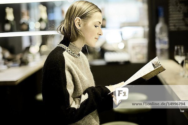Fashionable woman reading menu card at bar of restaurant  in Munich  Germany.