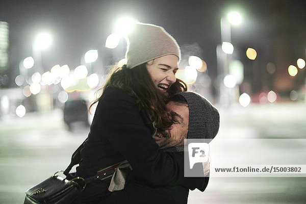 Couple falling in arms  embracing  laughing lovers outdoors in city at night  happiness  in Munich  Germany.