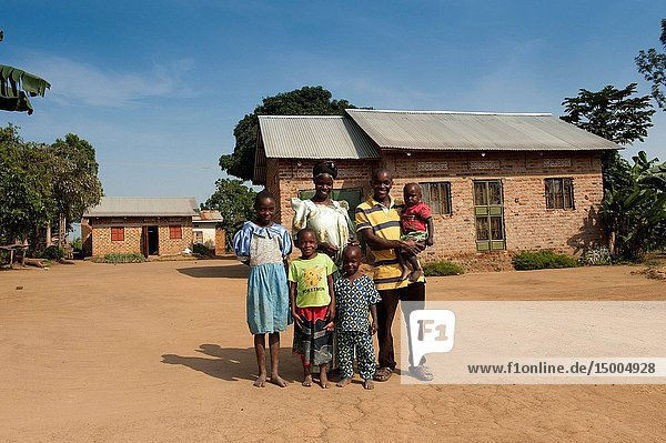 Prosperous and happy looking Ugandan family in front of their rural home.