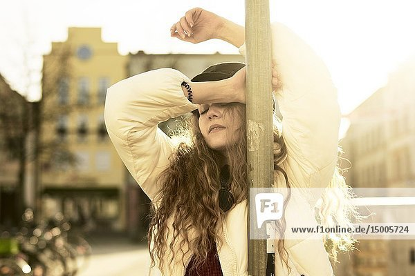 Young woman leaning on lamp post at street  sensual relaxed  in city Cottbus  Brandenburg  Germany.