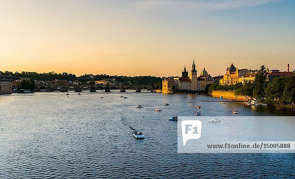 Sunset view of Moldava river full of boats  with Charles Bridge in the background  Prague  Czech Republic