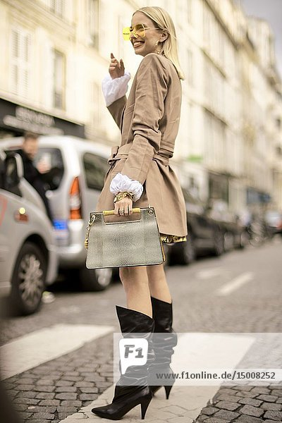 Street Style - Paris Fashion Week Womenswear Fall/Winter 2019/2020  fashion blogger Leonie Hanne wearing yellow sunglasses  a blazer jacket  a golden necklace  a white top  a yellow pvc snake print skirt  a gray bag  black boots  seen outside Elie Saab  Day six  March 2  2019.