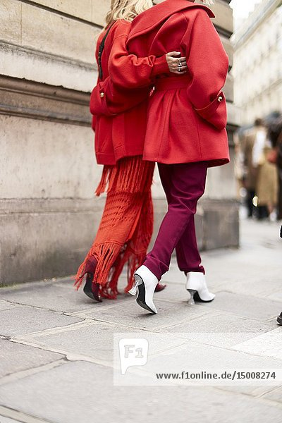 Street Style - Paris Fashion Week Womenswear Fall/Winter 2019/2020  red outfit  Charlotte Groeneveld (left) wears a red jacket  a red fringed dress  Balenciaga shoes  a black leather bag   Xenia Adonts (right) wears a red jacket  red pants  white shoes  seen outside Elie Saab  Day six  March 2  2019.