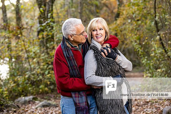 A happy 65 year old man and a 59 year old blond woman hugging in a forest setting.