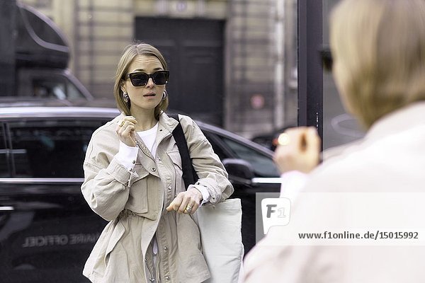 Fashionable woman looking at herself in window pane at street in front of black car  in Paris  France.
