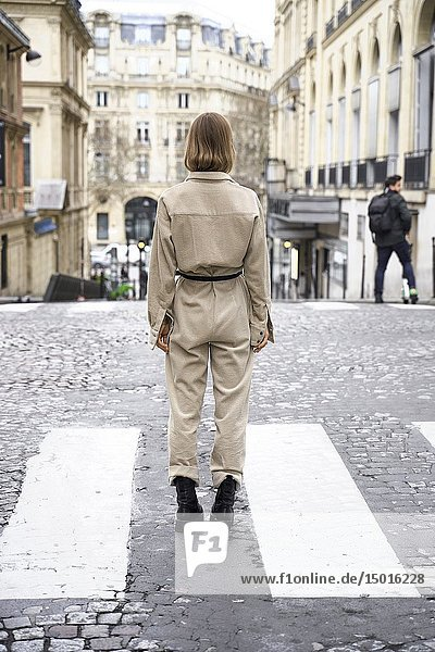 Back of fashionable woman standing in street  in Paris  France.