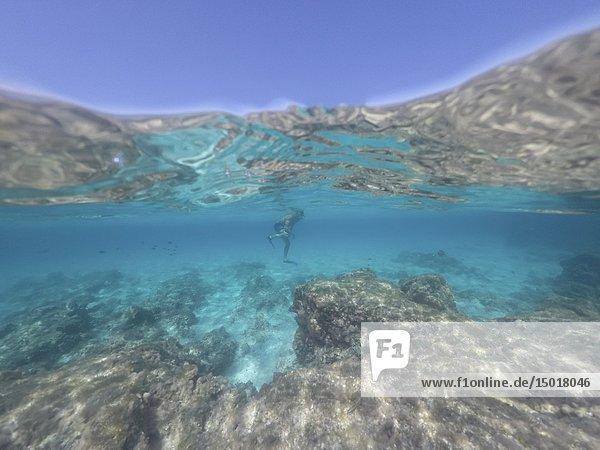 Young man in snorkelling mask dive Underwater El Calo de San Agusti Formentera island Balearics Spain.