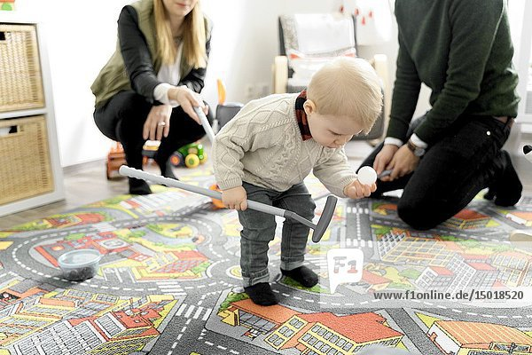 Baby toddler child next to parents in children's room  holding golf ball  standing on child's game carpet with printed streets  in Cottbus  Brandenburg  Germany.