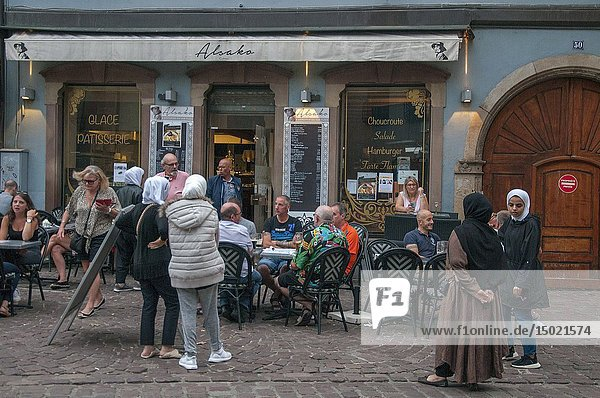 Two female Muslim tourists observe the behaviour of patrons at a tourist bar in Colmar  Alsace  France