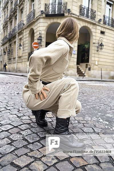 Cool unrecognisable fashionable woman crouching at street during fashion week  looking away  in Paris  France.