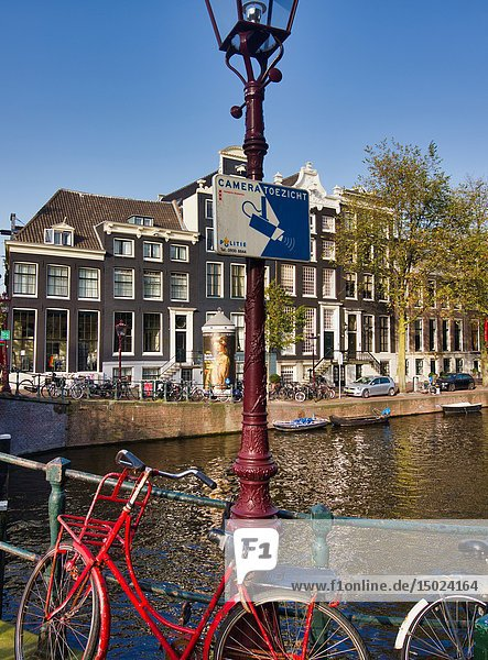 Camera surveillance sign on bridge over canal and red sit up and beg bike  Amsterdam  Holland  Europe