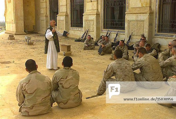 IRAQ Tikrit -- 09 Apr 2003 -- 7th US Marine Corps Regiment Chaplin  Father Bill Devine  speaks to Marines from 5th US Marine Regiment during Catholic Mass at one of Saddam Hussein's palaces in Tikrit  Iraq during the invasion of Iraq. USMC photo (Released) -- Picture by Andrew Roufs / Lightroom Photos / USMC.