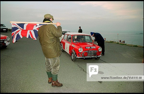 UK Land's End -- 06 Dec 2003 -- Mr John Brown waves a union flag to see off Tony Arnold and navigator Robert Ellis  accelerate away from the start of the LE JOG 2003 (The Land's End to John O'Groats Historic Reliability Trial) in their 1965 Austin Mini Cooper sports car. The rally has been organized by HERO (Historic Endurance Rallying Organization  run by Mr Brown - pictured with flag) and some 78 classic cars will be in the rally  with another 22 on the Touring Trial. All will travel the 1600 miles to John O'Groats finishing on 09 Dec -- Picture © Jon Mitchell / Lightroom.
