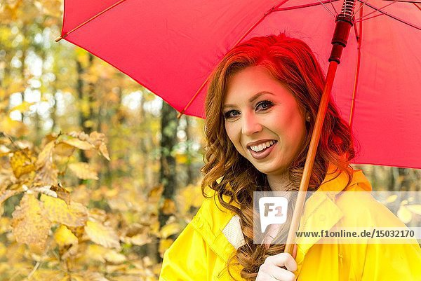 A 25 year old redheaded woman wearing a yellow jacket and carrying a red umbrella smiling at the camera.