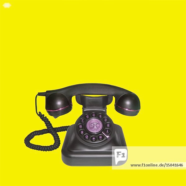 Ringing Antique Telephone against Yellow Background