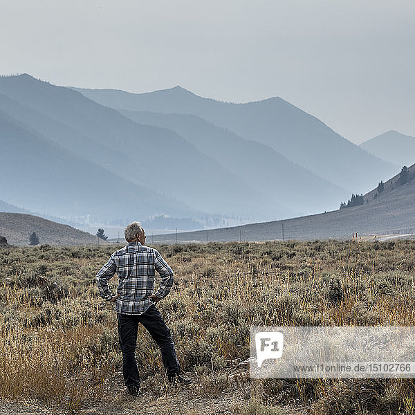 Senior man standing in field by mountains in Sun Valley  Idaho  USA