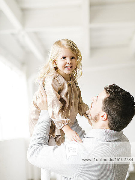 Mid adult man lifting his daughter