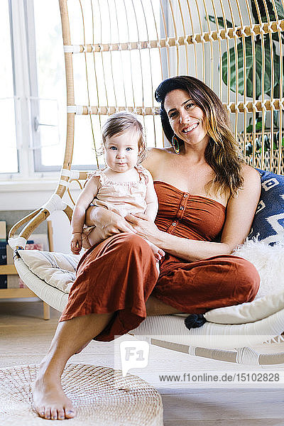 Woman with her baby daughter smiling on hanging chair