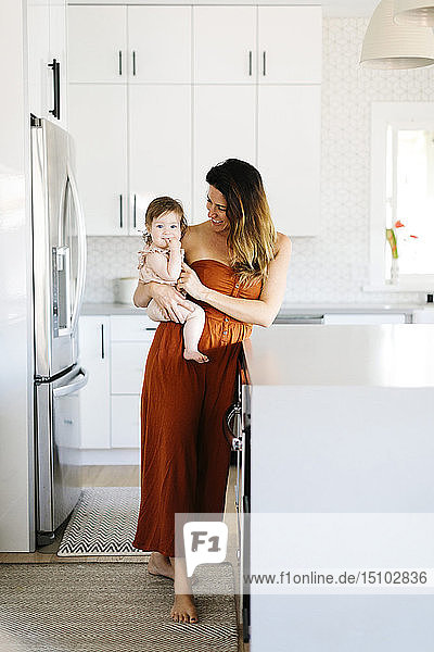 Woman carrying her baby daughter in kitchen