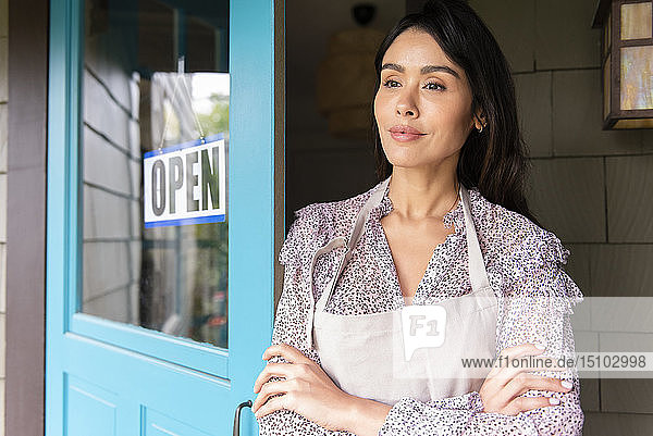 Woman by door to shop with open sign