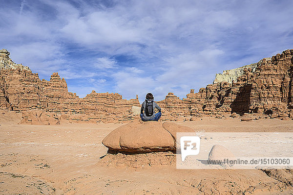 Woman sitting on rock in Goblin Valley State Park  Utah  USA