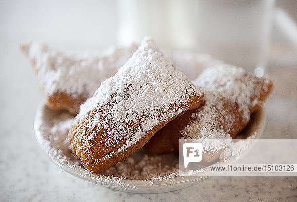 Beignets with powdered sugar on plate