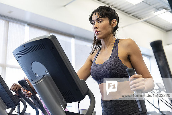 Woman exercising on elliptical machine