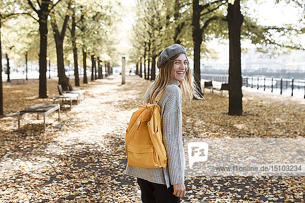 Young woman with yellow backpack in park in Berlin  Germany