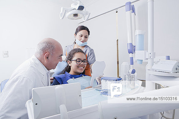 Patient smiling at mirror in dentist's surgery