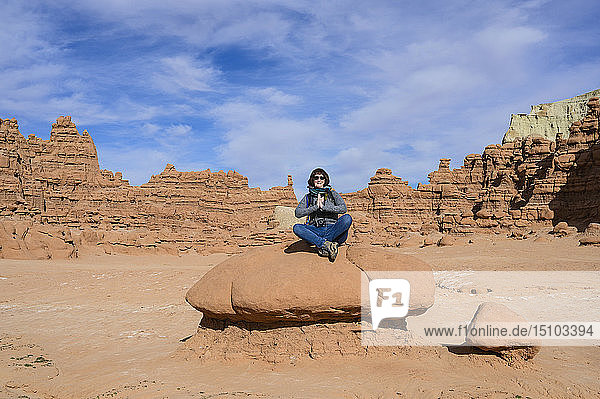 Woman meditating on rock in Goblin Valley State Park  Utah  USA