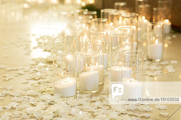 Lit white candles and petals
