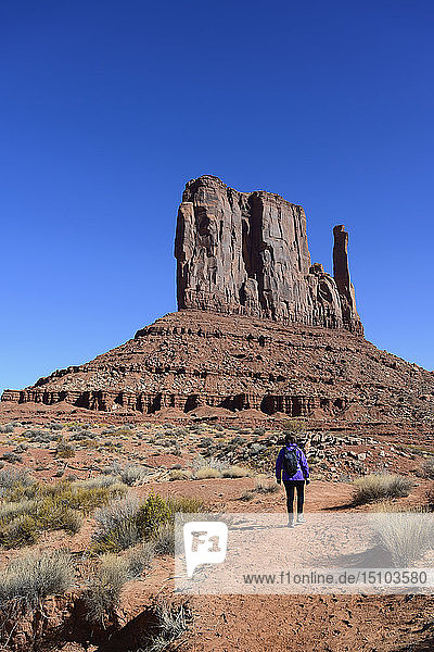 Woman hiking by butte in Monument Valley  Arizona  USA