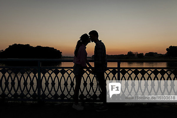 Silhouettes of young couple kissing at sunset