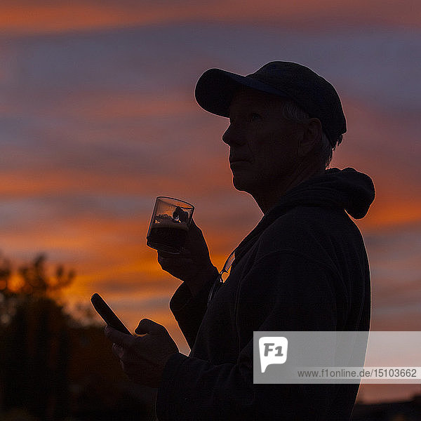 Silhouette of man holding coffee cup and smart phone at sunset