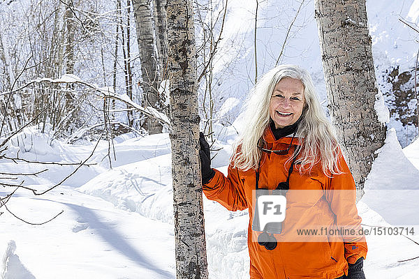 Mature woman wearing orange coat by bare trees in snow