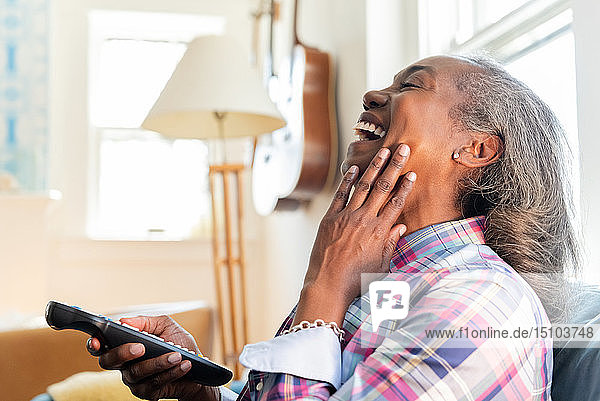 Mature woman with remote control watching television