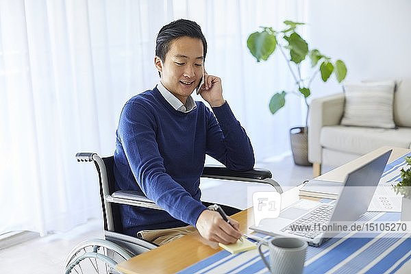 Japanese young man on wheelchair working from home