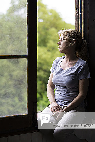 Thoughtful woman sitting on window