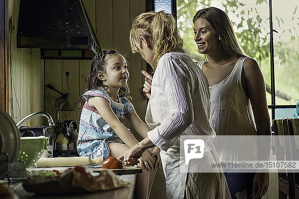 Mature woman talking her granddaughter in kitchen