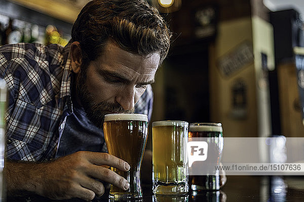 Close-up of man smelling beer