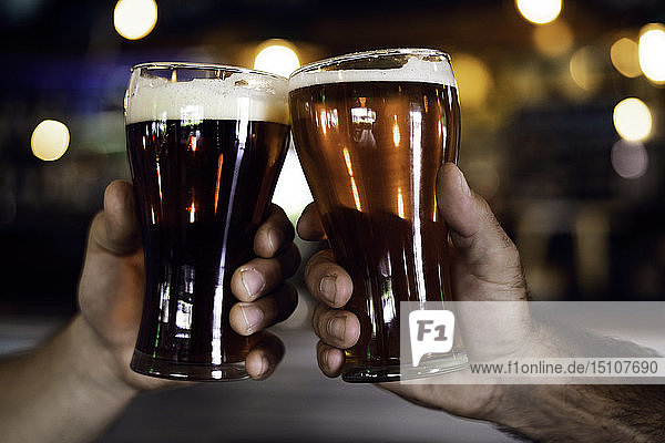 Hands toasting beer glasses