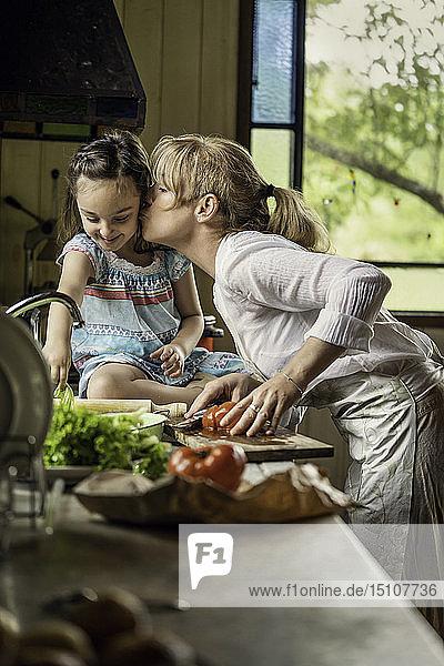 Mature woman kissing her granddaughter