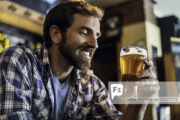 Man looking at beer glass