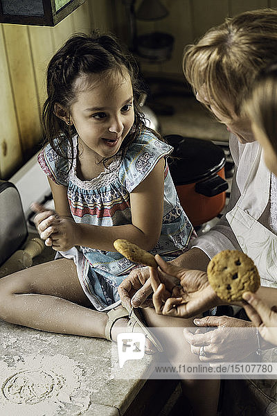 Girl with her mother and grandmother sitting in kitchen