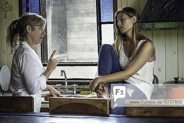 Mother and daughter talking in kitchen