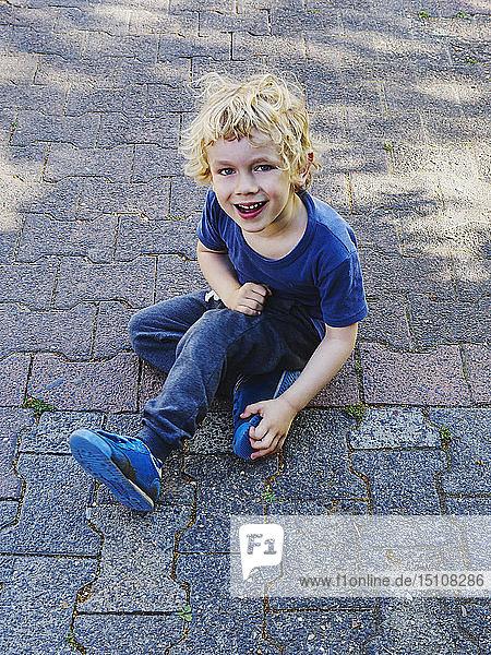 Porträt eines lächelnden  blau gekleideten kleinen Jungen auf dem Bürgersteig sitzend