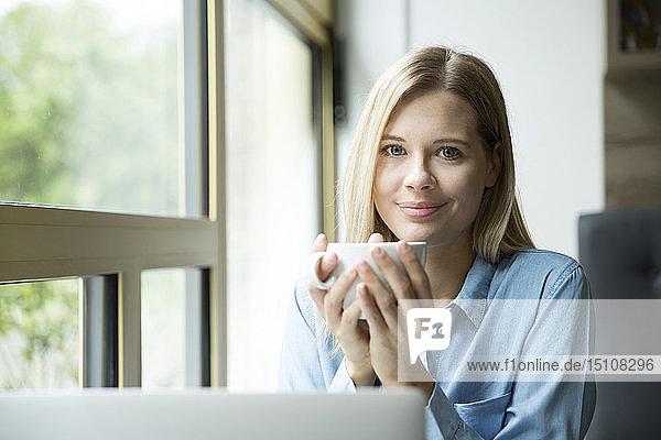Geschäftsfrau mit einer Tasse Kaffee  vor dem Laptop