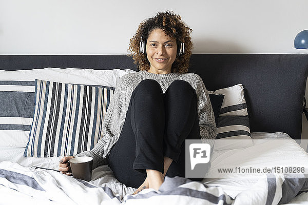 Woman sitting on bed  drinking coffee  listening music with headphones and smartphone